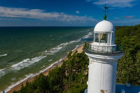 White Uzhava lighthouse on the shore of Baltic Sea. Sunny day. Reklamní fotografie