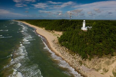 White Uzhava lighthouse on the shore of Baltic Sea. Sunny day. Banco de Imagens - 129015092