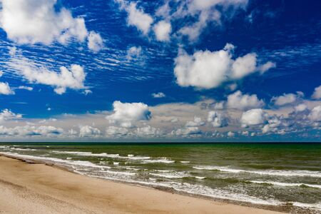 Beautiful view of the sea and the sand beach. Cloudy sky. Banco de Imagens - 129015101