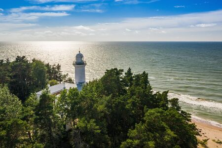 White Uzhava lighthouse on the shore of Baltic Sea. Sunny day. Banco de Imagens - 129015114