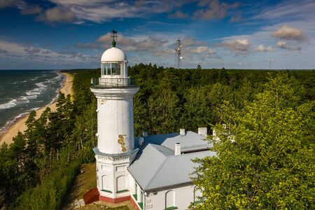 White Uzhava lighthouse on the shore of Baltic Sea. Sunny day. Banco de Imagens