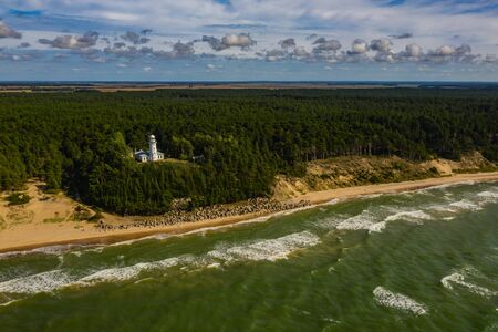 White Uzhava lighthouse on the shore of Baltic Sea. Sunny day. Banco de Imagens - 129015353