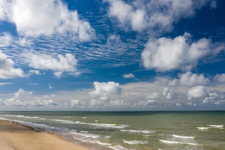 Beautiful view of the sea and the sand beach. Cloudy sky.