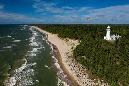 White Uzhava lighthouse on the shore of Baltic Sea. Sunny day. Banco de Imagens - 129015379