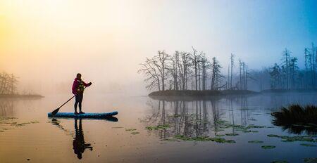 Atmospheric landscape. Fog over swamp. Sup-boarding. Banco de Imagens