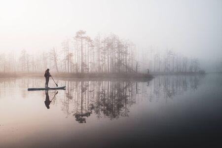 Atmospheric landscape. Fog over swamp. Sup-boarding. Banco de Imagens - 131556445