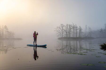 Atmospheric landscape. Fog over swamp. Sup-boarding. Reklamní fotografie