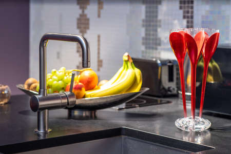 Close-up of sink in modern kitchen interior. Fruits in plate. Banco de Imagens