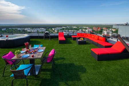 Rooftop terrace with green grass. Laid table and cozy couch. View of city from the top. Banco de Imagens