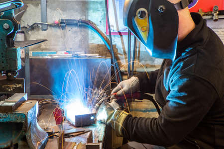 Electric welding process. Worker in welding mask. Yellow sparks fly to the sides. Bright white.