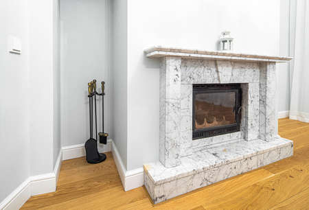 The marble fireplace in living room. Modern luxury interior in light tones.