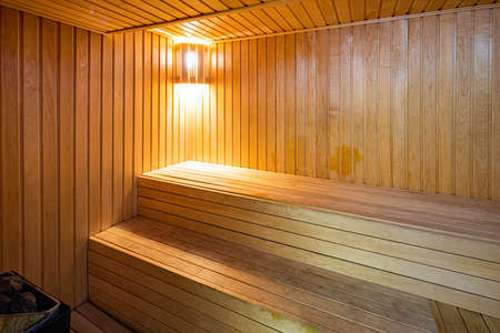 Beautiful and clean wooden finnish sauna. Modern bathroom for hot spa treatments. Banco de Imagens