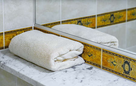 A white folded towel on a marble shelf next to the mirror. Close-up. Banco de Imagens