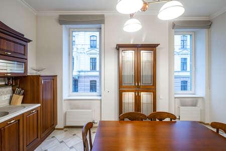 Luxury interior of kitchen in modern apartment. Wooden furniture. Windows.