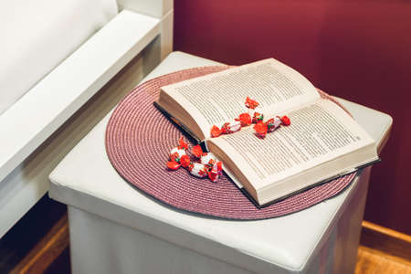 Close-up of the composition of book and sweets on the bedside. Banco de Imagens