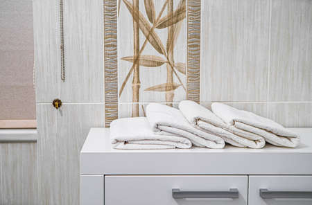 Close-up of white folded towels on the white dresser in modern bathroom.