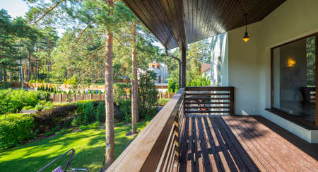 Modern exterior of luxury private house. Wooden terrace. Green garden at sunny day. Banco de Imagens