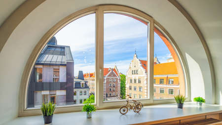 Close-up of arch semicircle window. View of old town of Riga, Latvia. Sill with flowers and decorative bicycle. Modern interior. Banco de Imagens