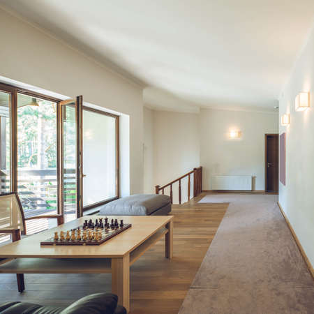 Light contemporary interior of private house. Wooden furniture. Table with chess. Glass door to terrace. White walls. Banco de Imagens