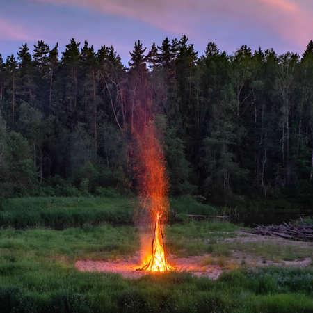 Traditional midsummer Ligo celebration. Huge bonfire on the river shore. Scenic landscape of forest at twilight. Sunset sky.
