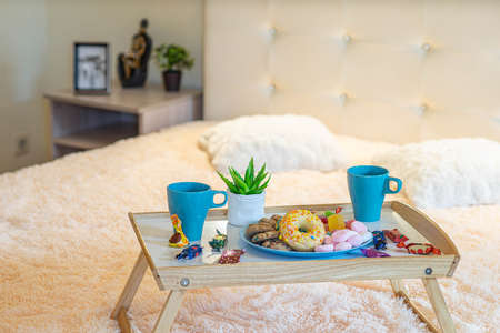 Close-up of tray with breakfast on the bed. Romantic composition. Couple of mugs, sweets and donut. Banco de Imagens
