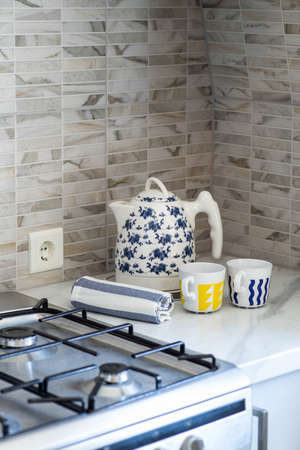 Close-up of blue and white electric kettle with couple of mugs and towel. White surface. Banco de Imagens
