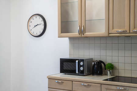 Modern interior of kitchen. Stylish kitchen set. Clock on the wall. Close-up of black microwave and kettle. Banco de Imagens