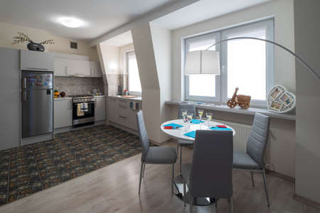 Light interior of kitchen in studio apartment. Kitchen set. Table and chairs. Wall with windows. Foto de archivo