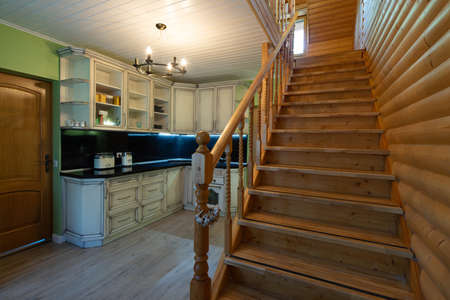 Kitchen in private house. Staircase to the second floor. Modern wooden interior. Kitchen set and home appliances.