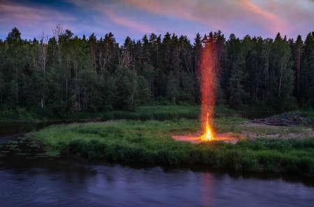 Landscape of pine forest and river. Sunset sky. Huge fire. Midsummer Ligo celebration. Latvian traditions.