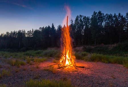 Traditional midsummer Ligo celebration in Latvia. Huge bonfire. Scenic landscape of forest at twilight. Sunset sky.