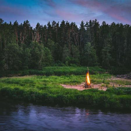 Midsummer Ligo celebration. Huge fire on the river shore. Scenic landscape of forest at twilight.