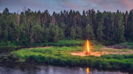 Traditional midsummer Ligo celebration. Huge fire on the river shore. Scenic landscape of forest at twilight.