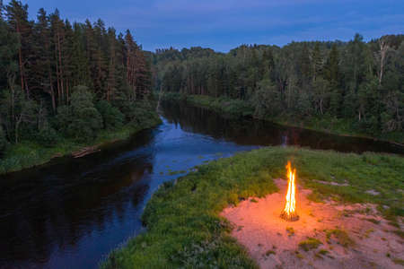 Landscape of forest and river at white night. Huge fire. View from above. Midsummer Ligo celebration. Stockfoto