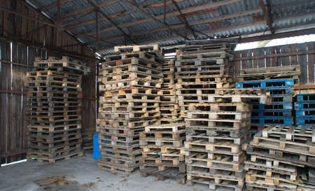 Wooden pallets stacked on top of each other inside the warehouse. Wooden walls. Banque d'images