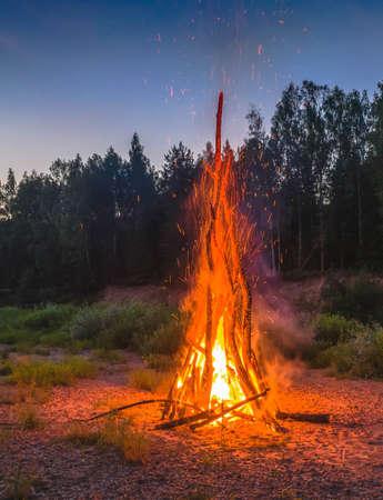 Traditional midsummer Ligo celebration in Latvia. Huge bonfire. Scenic landscape of forest at white night. Sunset sky.