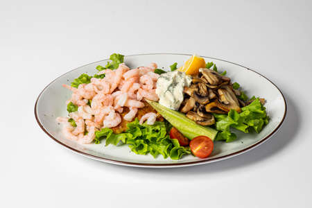 Close-up of delicious food isolated on white. Prawns, fried mushrooms and greens with sauce. Banco de Imagens