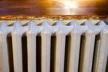 Close-up of white heating battery in apartment. Wooden sill.
