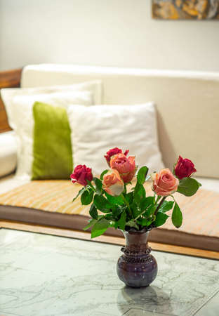 Close-up of flowers in the vase on the table in interior. Beautiful roses.