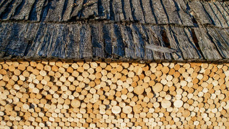 Wood in a woodpile, stacked under an old wooden tile roof. Banco de Imagens