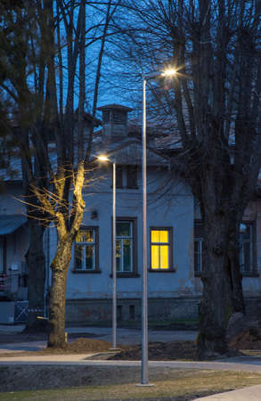 City lighting in the evening time. Residential building. Modern lanterns. Banco de Imagens