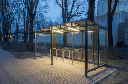 Modern parking space for bicycles, equipped with lighting. Evening time. Banco de Imagens