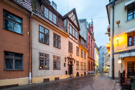 An architecture of Old town in Riga, Latvia. City lighting at evening time. Empty street. Banco de Imagens