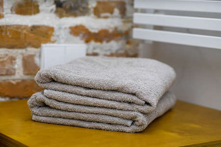 Spa composition. Folded gray towels in hotel bathroom. Loft interior. Brick wall.