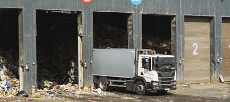 White garbage truck near gates of warehouse of garbage. Waste sorting. Recycling. Caring for environment.