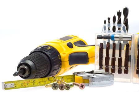 herramientas de trabajo: destornillador el�ctrico y equipo de acompa�amiento en un fondo blanco Foto de archivo