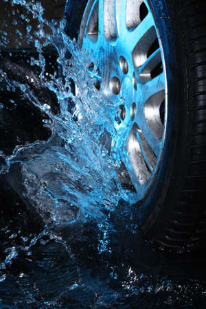 lavado: La rueda de coche con agua azul sobre fondo negro