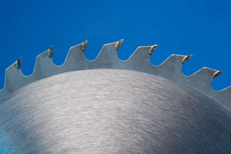 sharp curve: Saw blade on a blue background Stock Photo