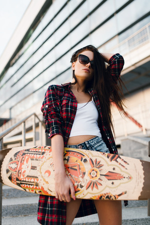 skateboarder: Happy beautiful woman in fashion sunglasses, casual clothing stay with wooden longboard skateboard in front of business or sport building. Cute hipster lady have fun. Urban scene, city lifestyle.