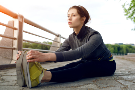 Yong female runner with beautiful figure doing stretching exercise before began her run
